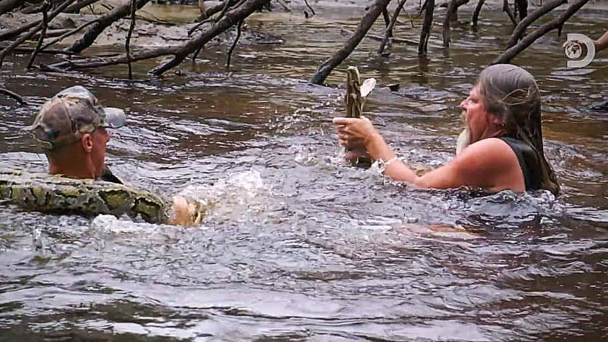 Dusty has dived under the water to grab this monster python on the exclusive peek at Tuesday's episode. Pic credit: Discovery.