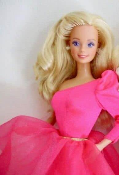 Day to Night Barbie is shown in a one-sleeved hot pink dress