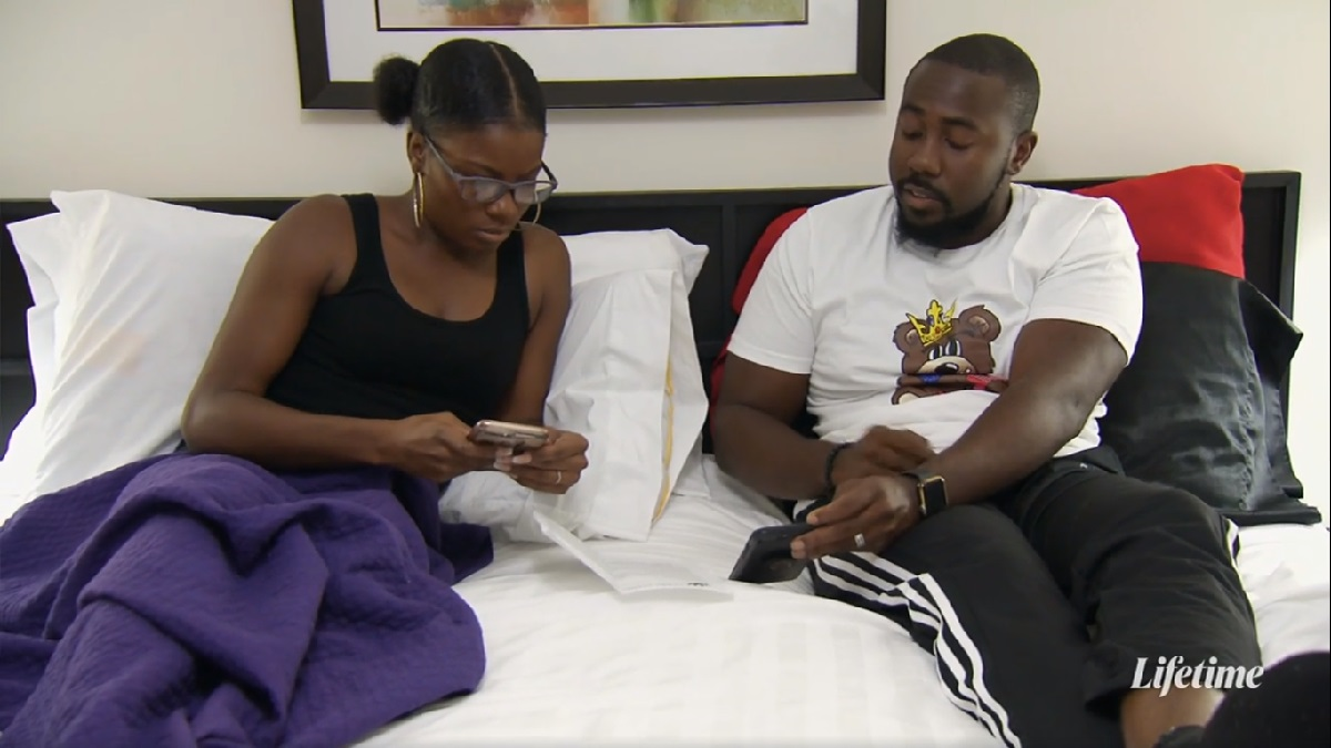Meka and Michael lay in bed showing pay stubs