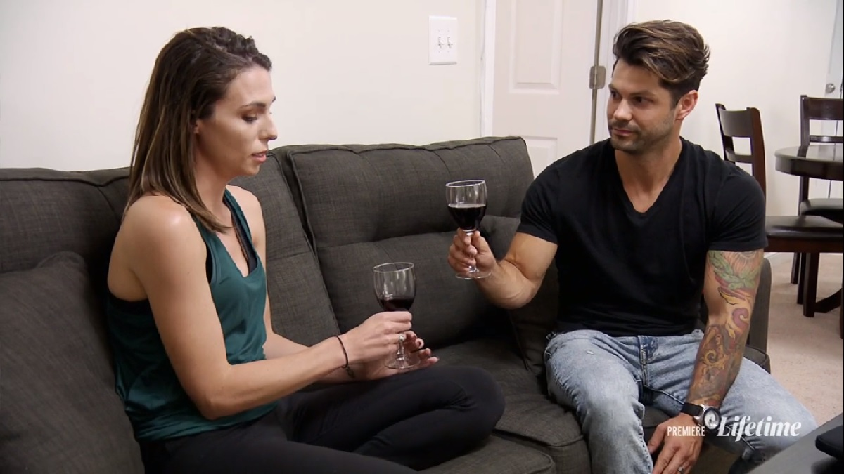 Zach and Mindy talk on the couch over wine