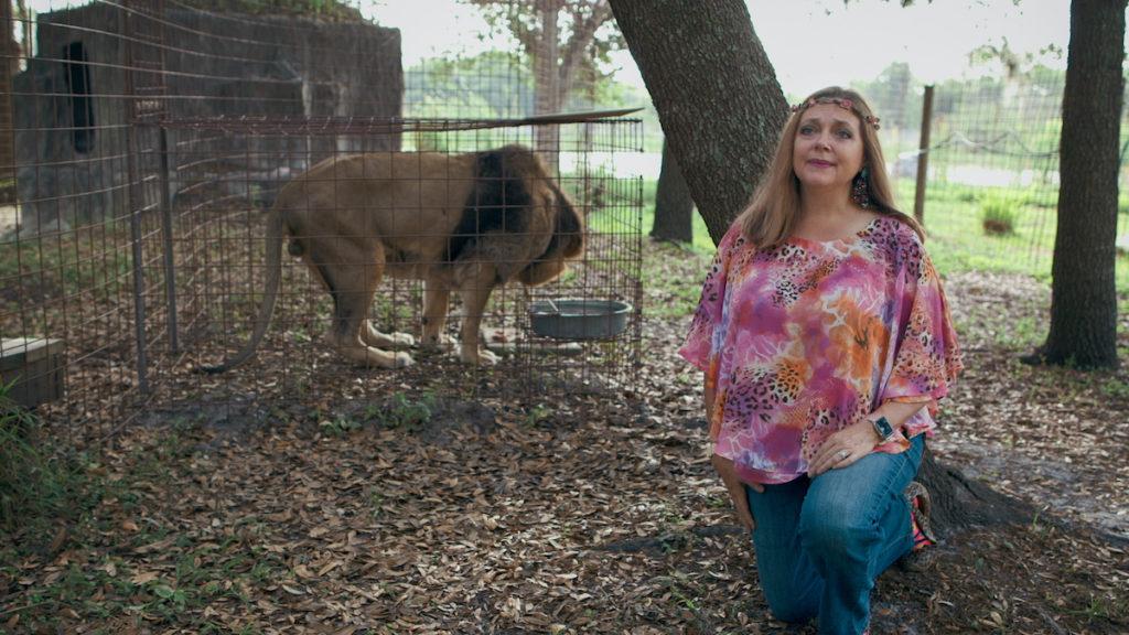Carol Baskin kneels near one of her lions