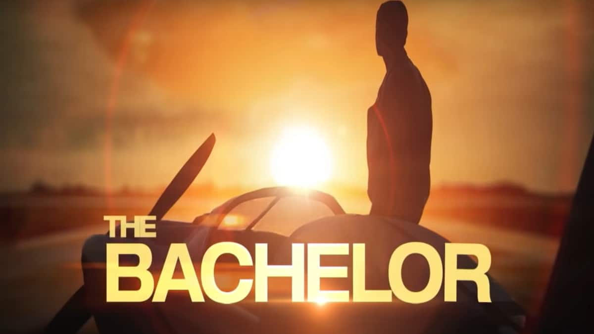 Season 24's Bachelor, Peter Weber, stands in silhouette in front of ain airplane