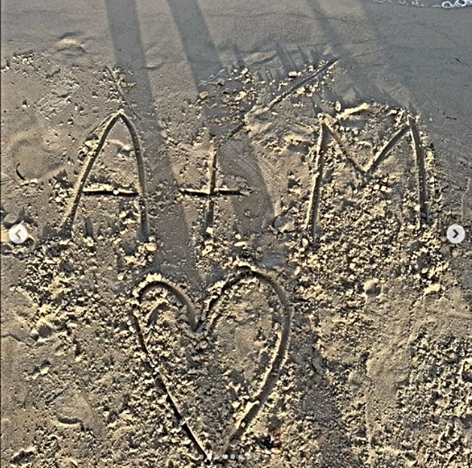 Aladin shares writes his fiance's initials in the sand