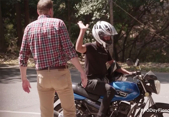 90 day fiance Tim standing in front of motorcyclist who has his hand up dismissively