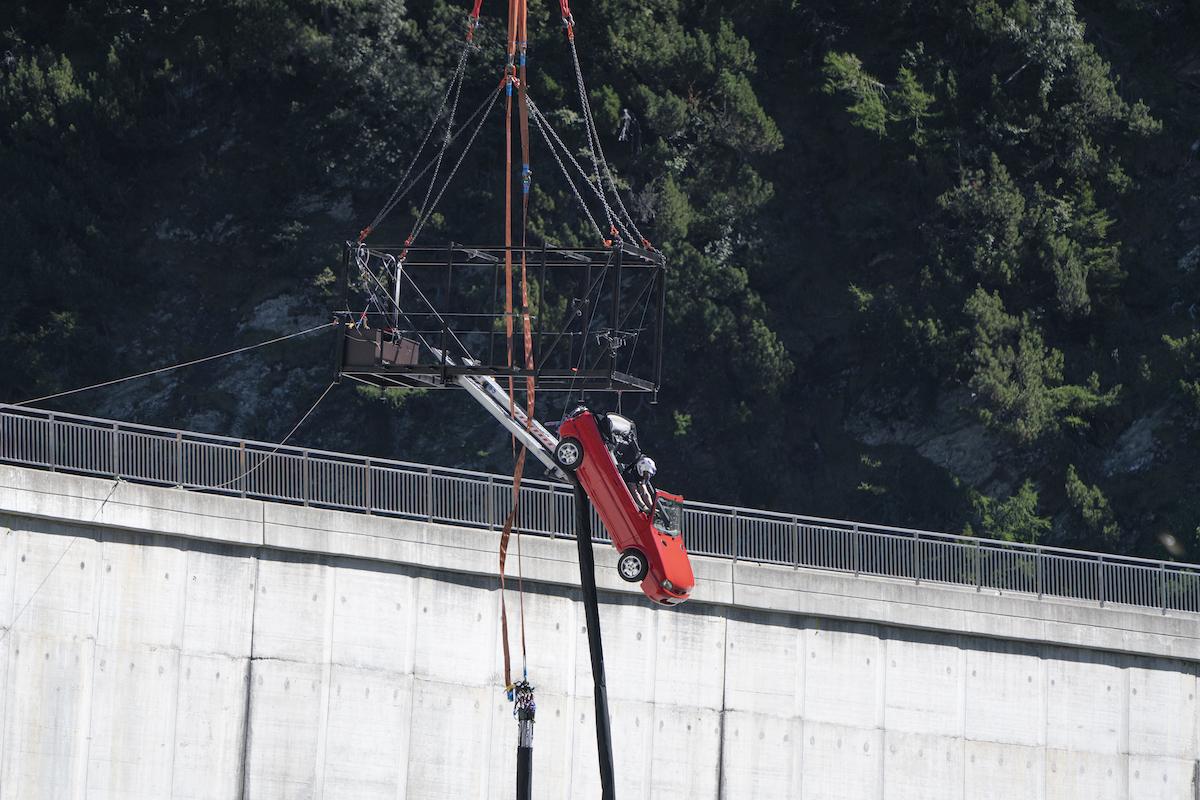 Car hanging above dam