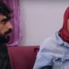 Yazan talks to Brittany while she sits on the couch in a hijab