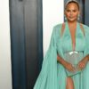 Chrissy Teigen poses in green dress