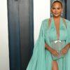 Chrissy Teigen poses in green dress