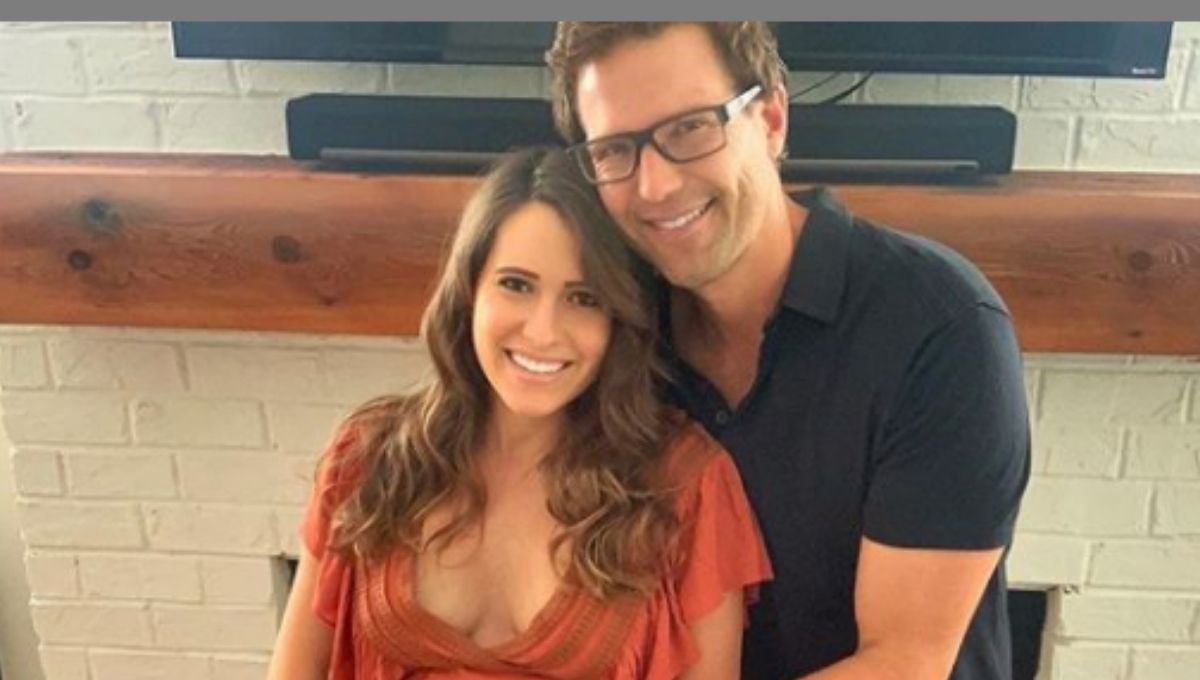 Travis Stork poses with his pregnant wife in front of a fireplace