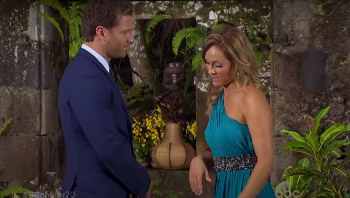 Juan Pablo in a suit standing in front of Clare Crawley in a blue dress