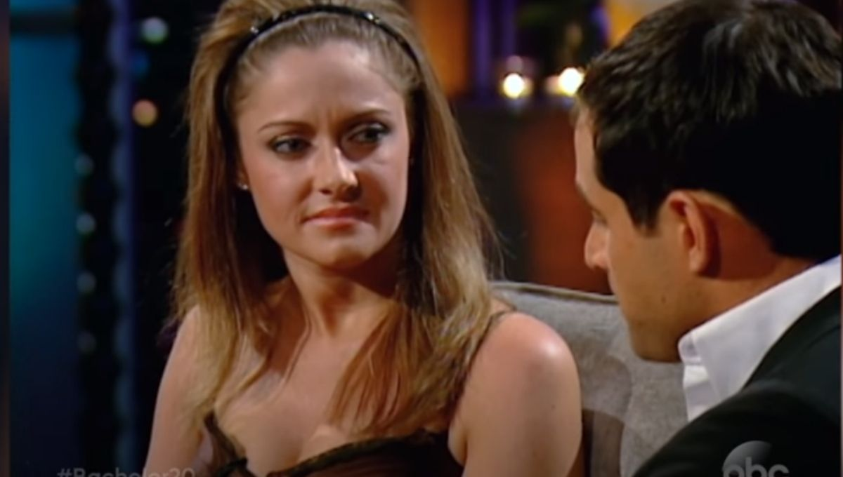 Molly Malaney in a black headband and dress looking seriously at Jason Mesnick