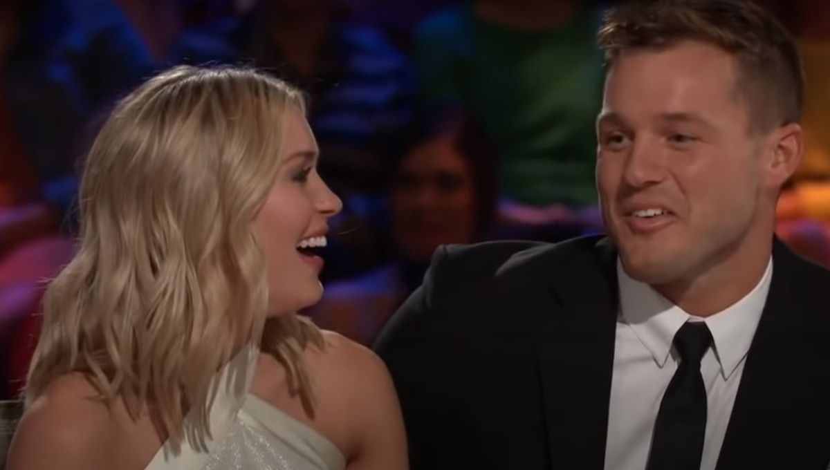 Cassie Randolph in a white dress smiling at Colton Underwood on the After the Final Rose couch