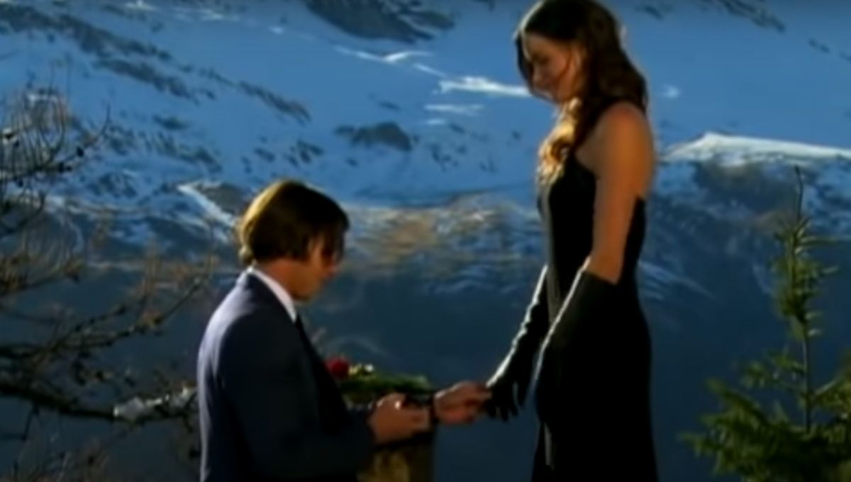 Ben Flajnik in a suit proposes to Courtney Robertson wearing a black dress and long black gloves against a mountain backdrop