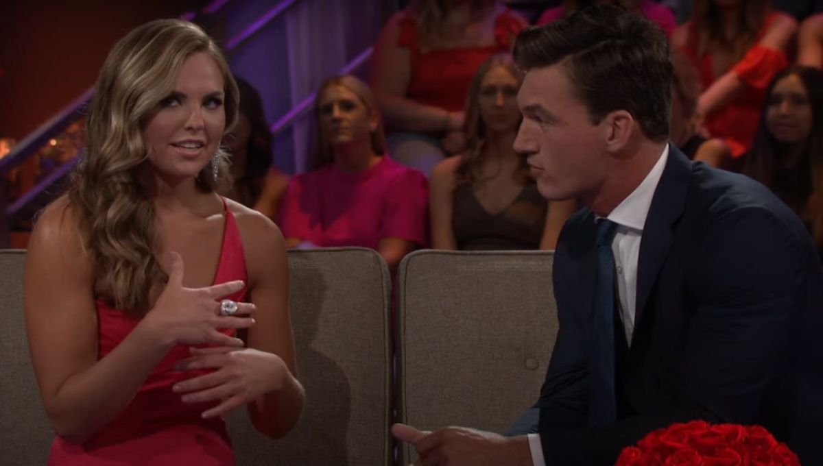 Hannah Brown in a red dress sitting next to Tyler Cameron on a couch