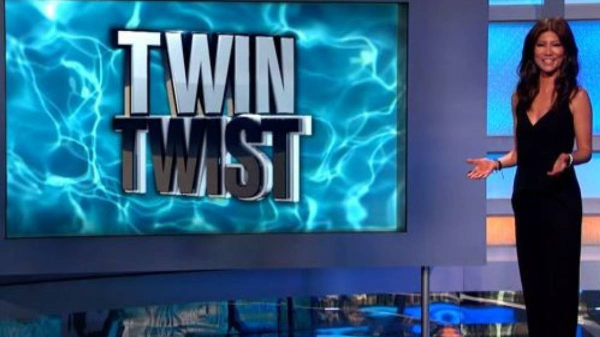 """Big Brother host Julie Chen stands in front of a screen that reads """"twin twist."""""""