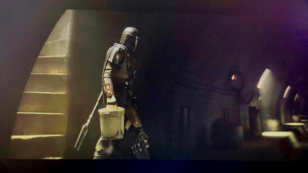 Mando enters a room carrying a round container in a scene from The Madalorian