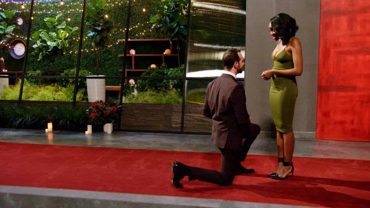 Cameron Hamilton kneels in front of Lauren Speed.