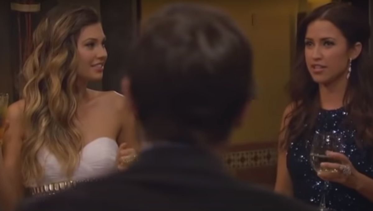 Britt Nilsson standing in a white dress next to Kaitlyn Bristowe in a black dress with a man's head in front