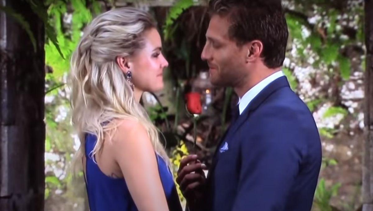 Nikki Ferrell in a blue dress standing in front of Juan Pablo Galavis holding a rose