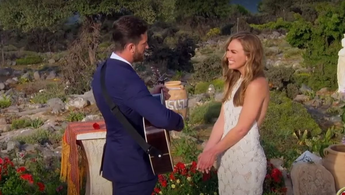 Hannah Brown standing in a white dress while Jed Wyatt plays his guitar and sings to her before his proposal