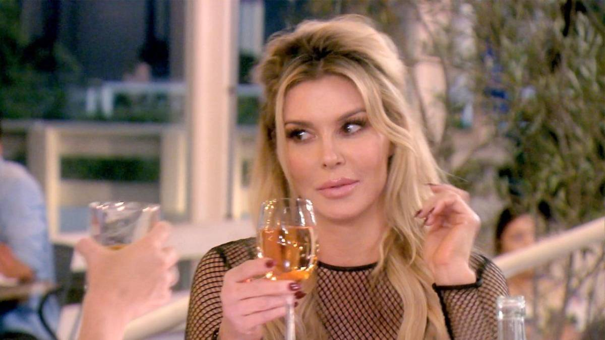 Brnadi Glanville holds a wine glass while filming RHOBH.