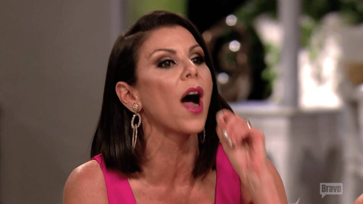 Heather Dubrow holds her hand up has she talks while filming RHOC.
