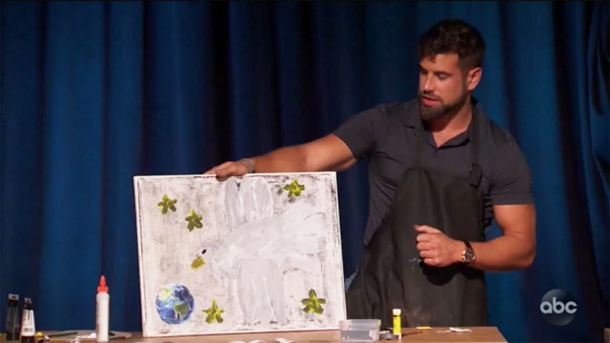 Blake from The Bachelorette holding up his turtledove painting