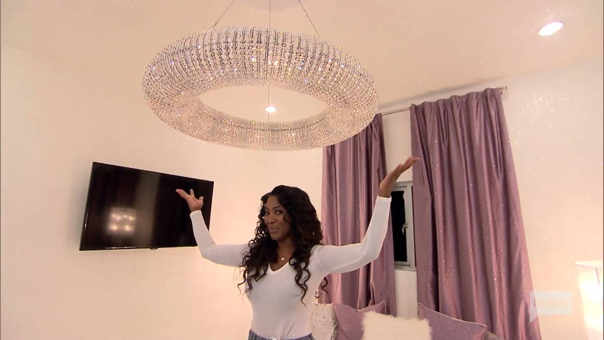 Kenya Moore poses under her chandelier while giving a tour of her home.
