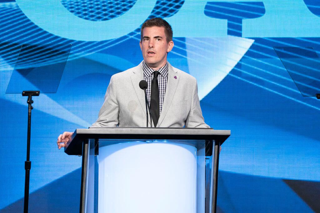 Andy Dehnart stands at a podium at an awards show
