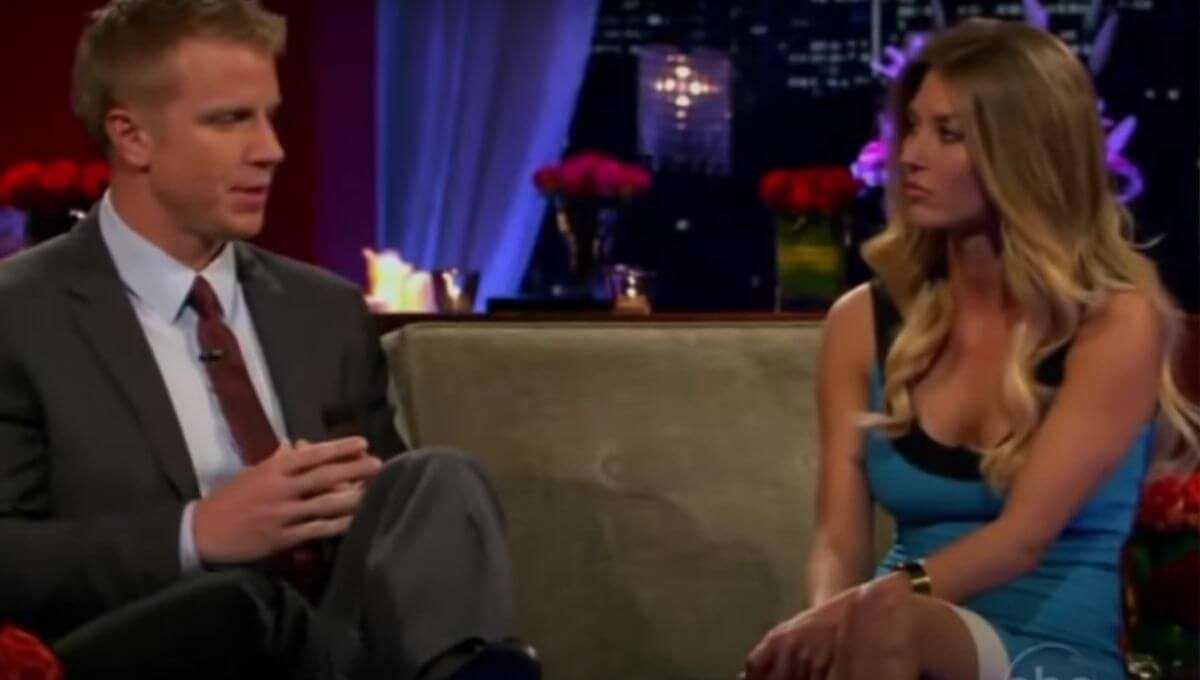 AshLee Frazier wearing a blue dress as she sits on the couch next to Sean Lowe