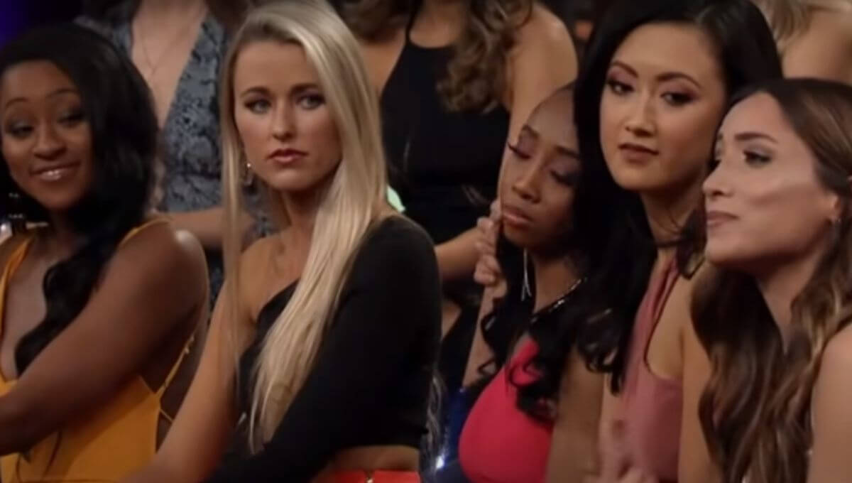 Onyeka and Nicole talk to each other amongst the other contestants during The Women Tell All