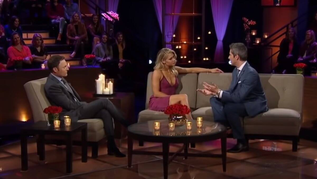 Krystal Nielson in a pink dress sits next to Arie Luyendyk Jr. on a couch during The Women Tell All