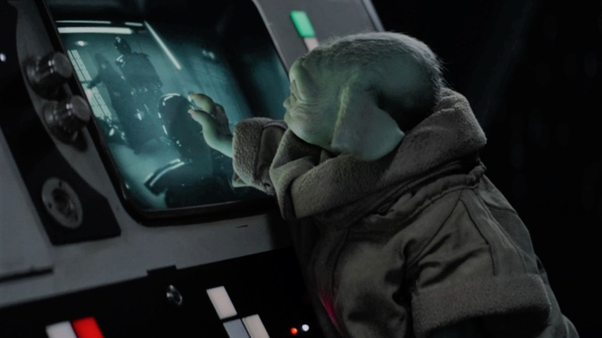 Grogu reaches out to a screen showing Luke Skywalker