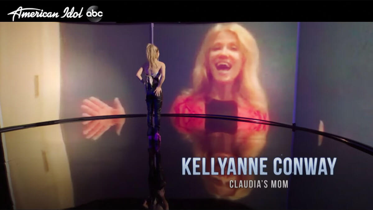 Kellyanne Conway is being projected on a large screen smiling, while Claudia stands in front of it.