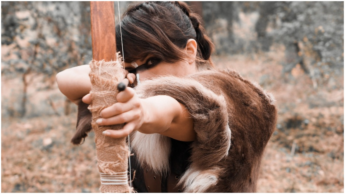 A Viking shieldmaiden draws a bow