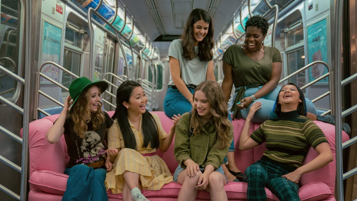 A picture from To All the Boys: Always and Forever of the characters sitting on a pink couch in the subway.