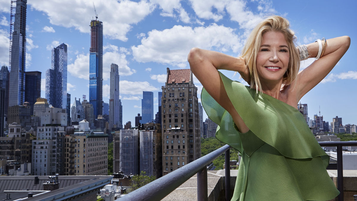 Candace Bushnell standing in front of a cityscape