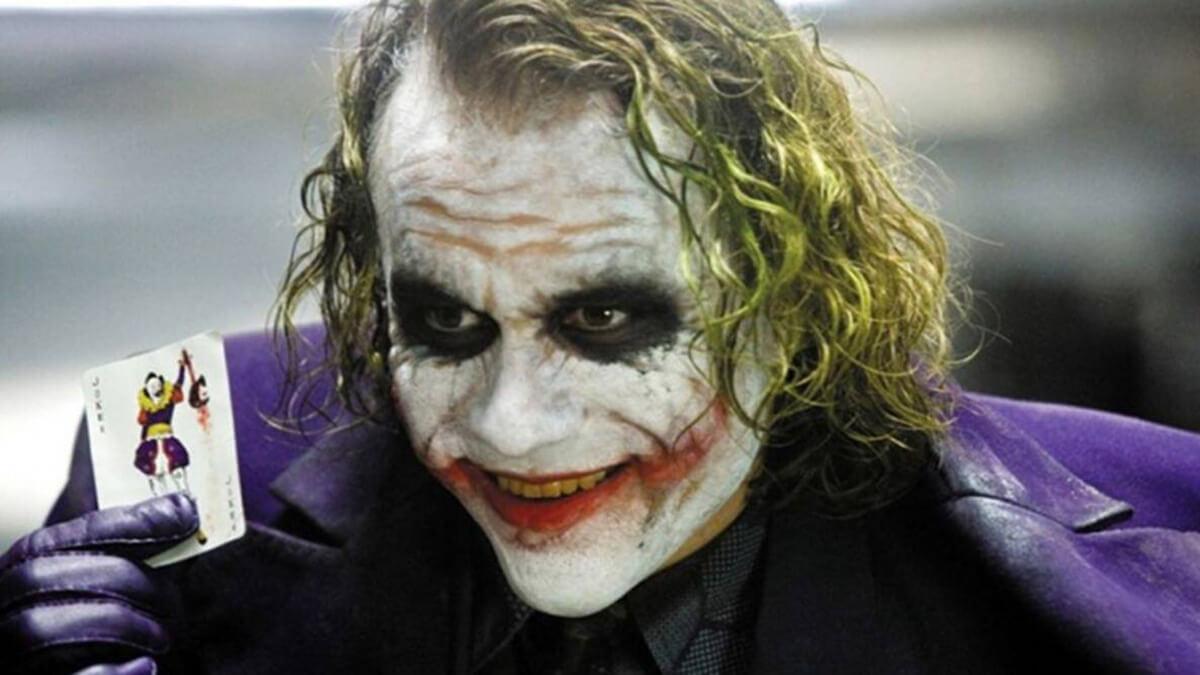 Joker holding up a card in Dark Knight