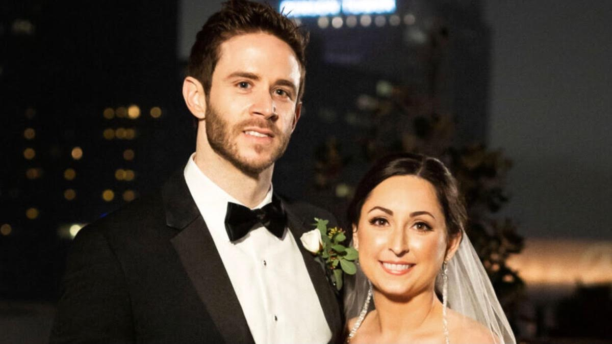 Brett and Olivia pose with a smile on their wedding day