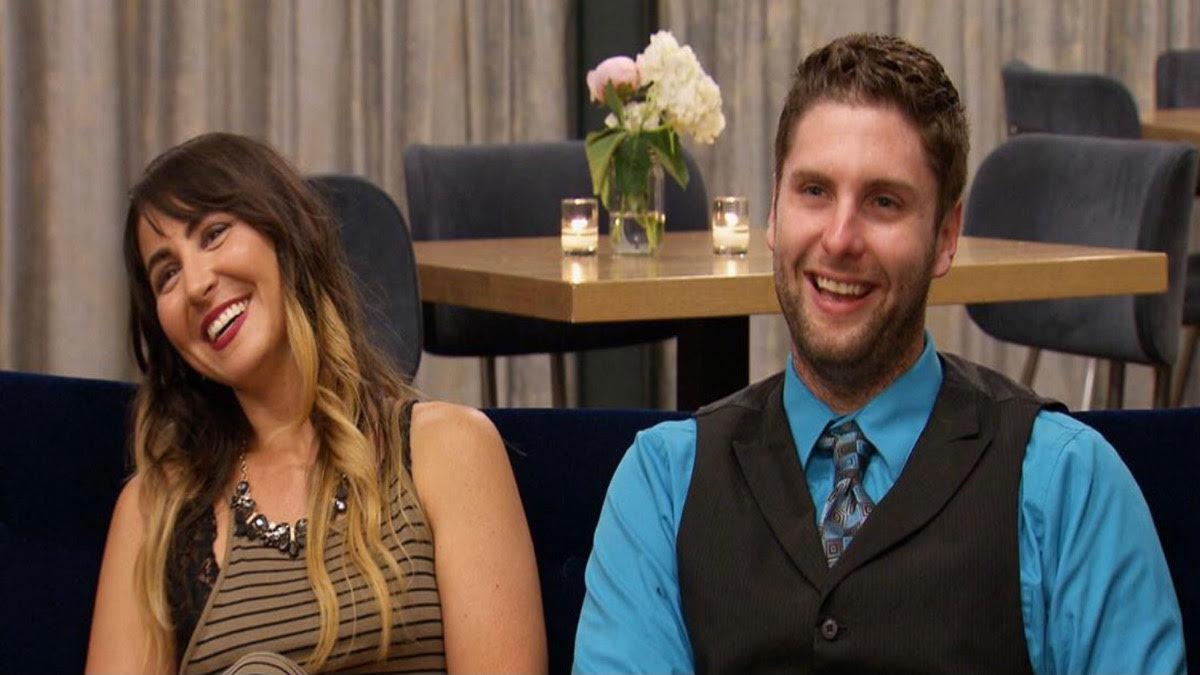 Cody and Danielle laugh while sitting on a couch