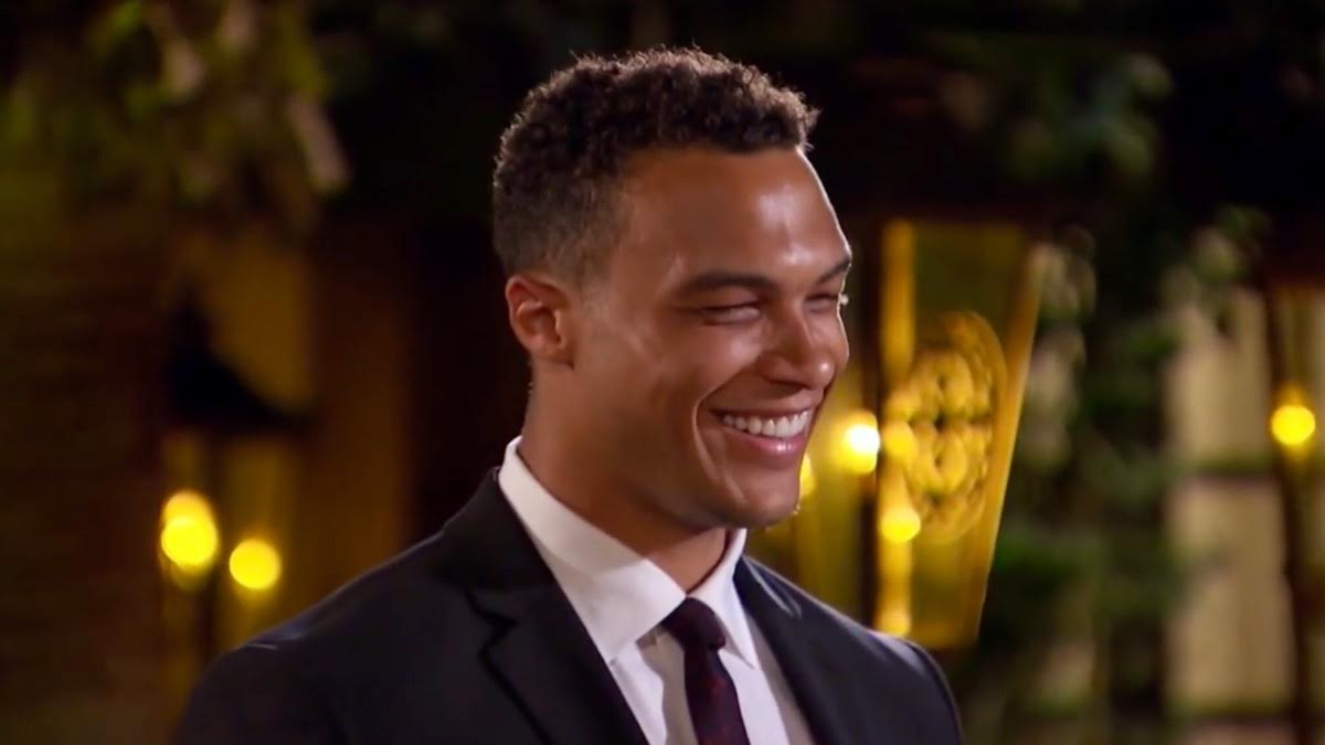Dale Moss wears a suit and tie and smiles before proposing