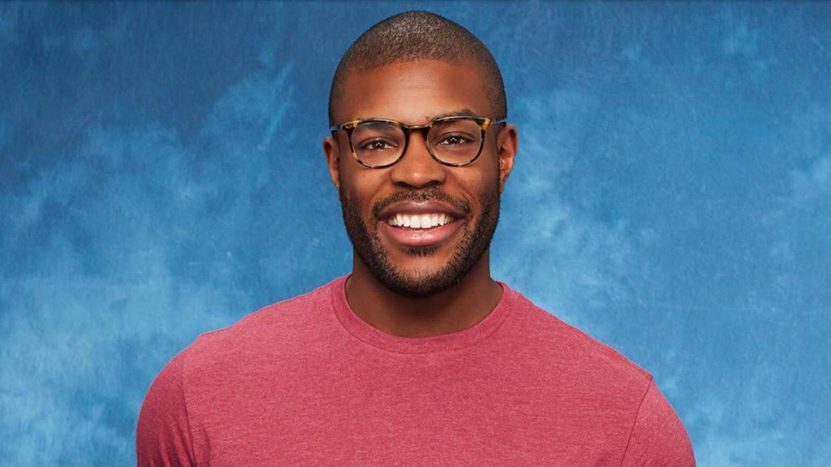 Diggy Moreland wears glasses and a red shirt while smiling
