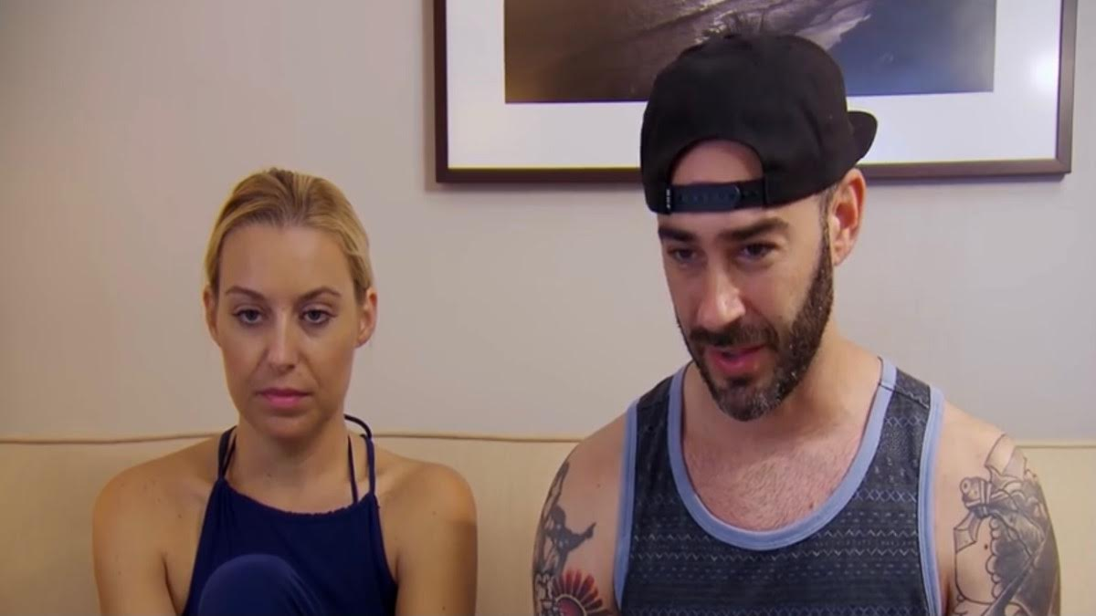 Heather and Derek sit on a couch in their hotel