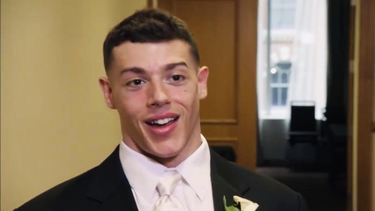 Jason Carrion looks in the camera wearing a suit and tie on his wedding day