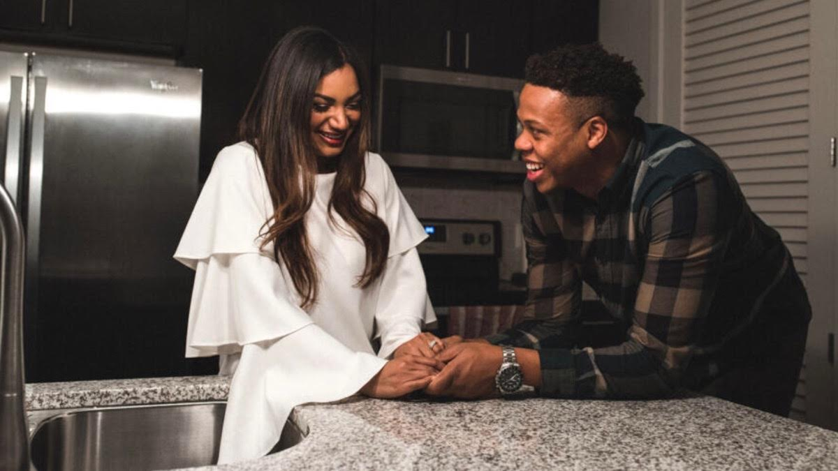 Mia and Tristan hold hands and smile in the kitchen