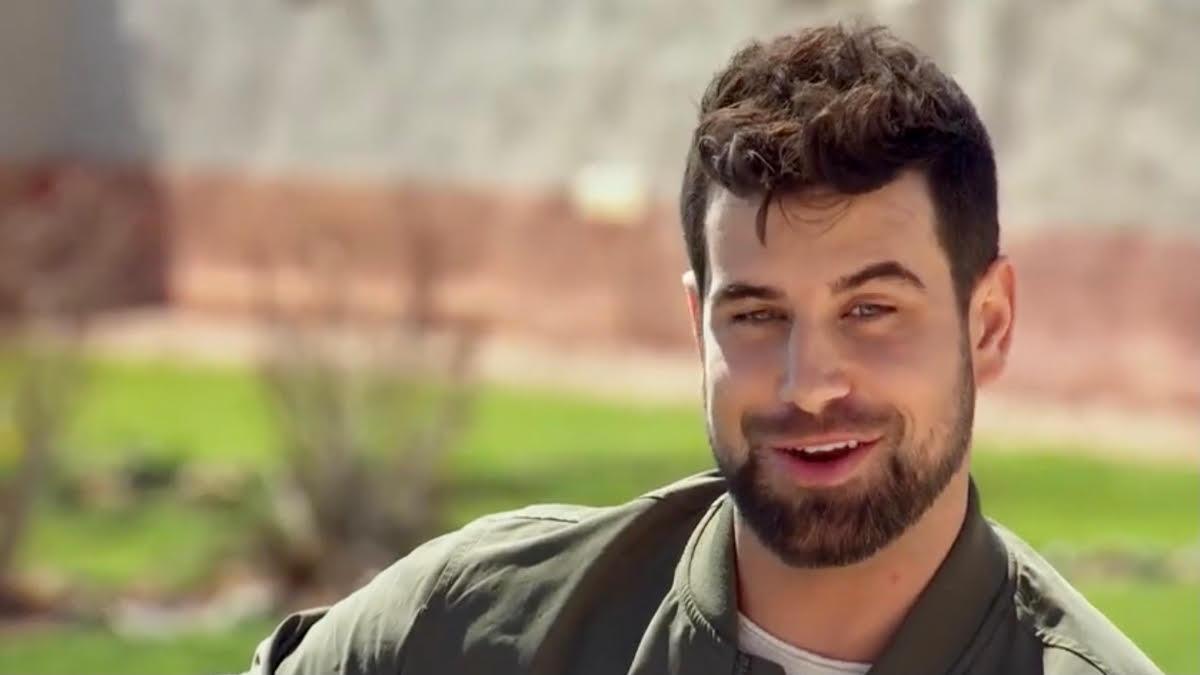 Blake Moynes smirks while outdoors