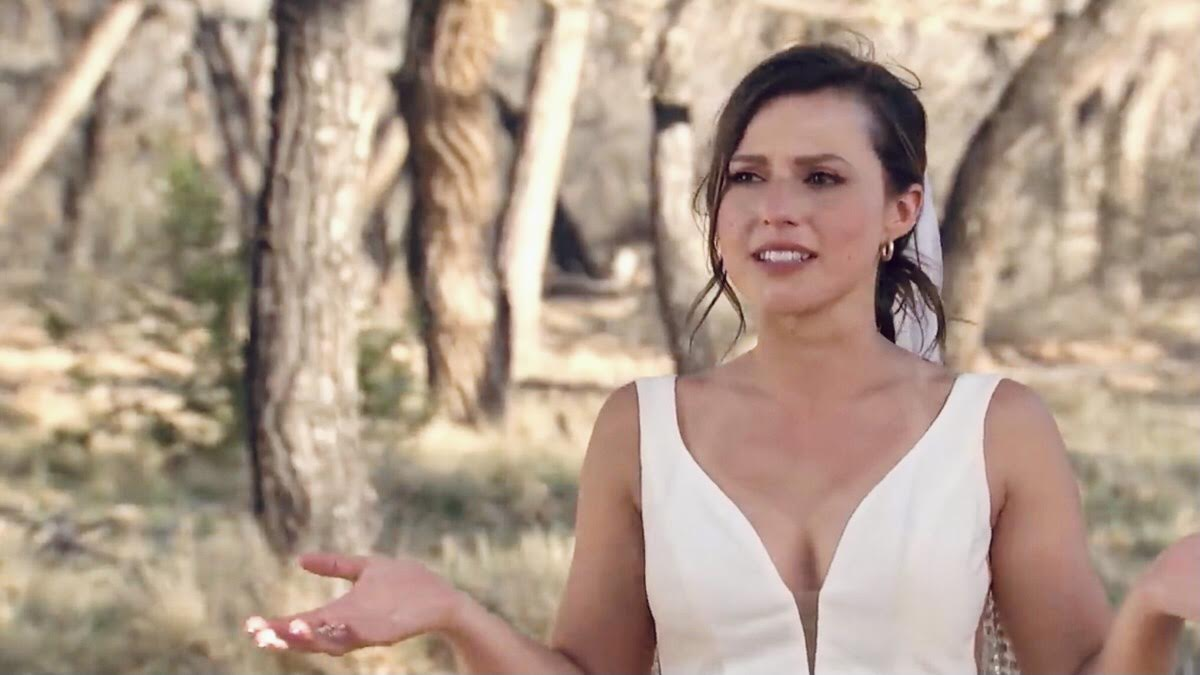 Katie Thurston wears a white wedding dress and earrings