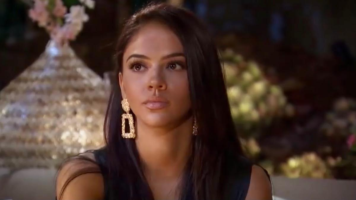 Sydney Hightower looks to the left and wears gold statement earrings